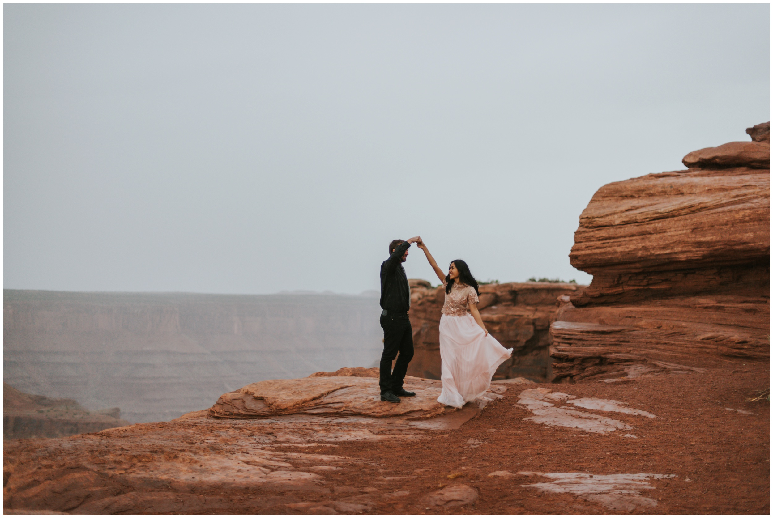 guy spinning girl ontop of dead horse point | Elopement Photographer www.riversandroadsphotography.com