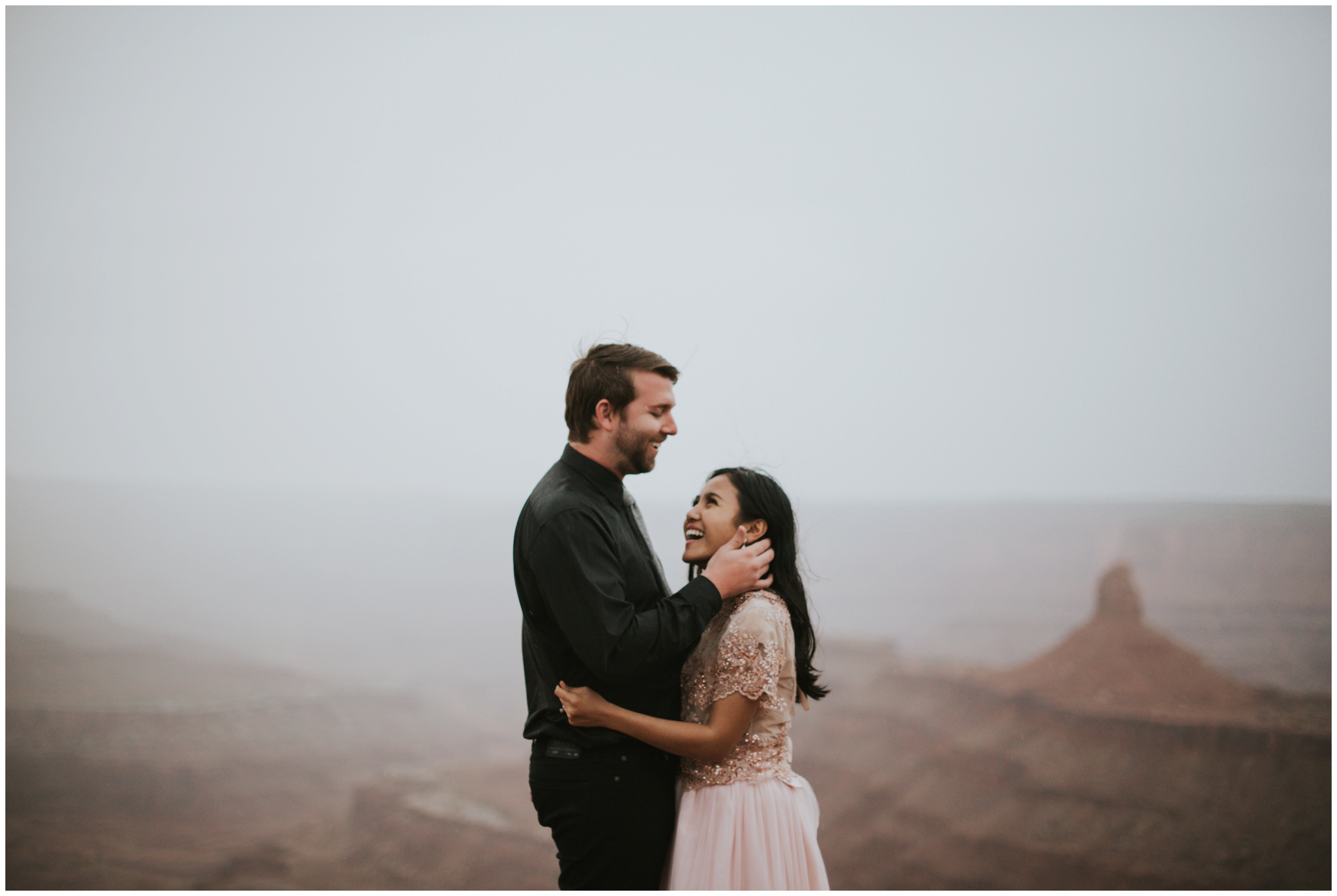 guy playing with girls hair on top of mountain | Elopement Photographer www.riversandroadsphotography.com