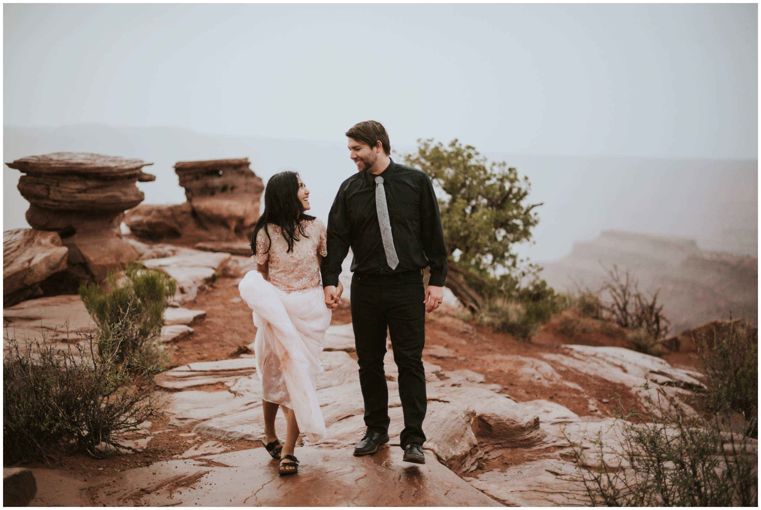 bride and groom embracing the elements rainy elopement at dead horse point state park | Elopement Photographer www.riversandroadsphotography.com