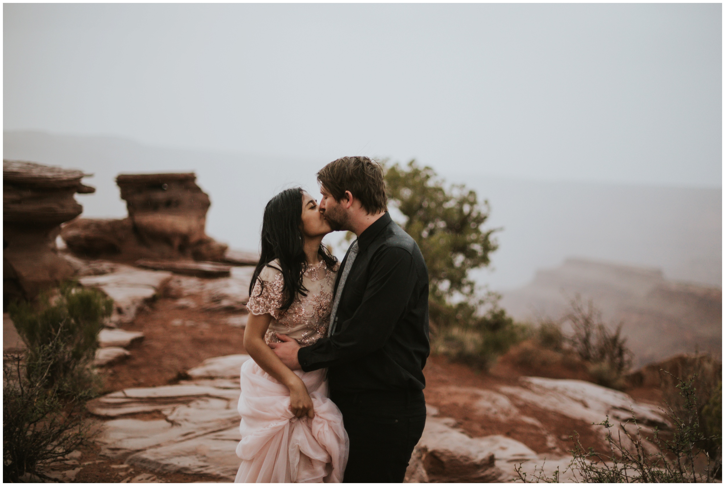 bride and groom kiss in the rain elopement at dead horse point state park overlook | Elopement Photographer www.riversandroadsphotography.com