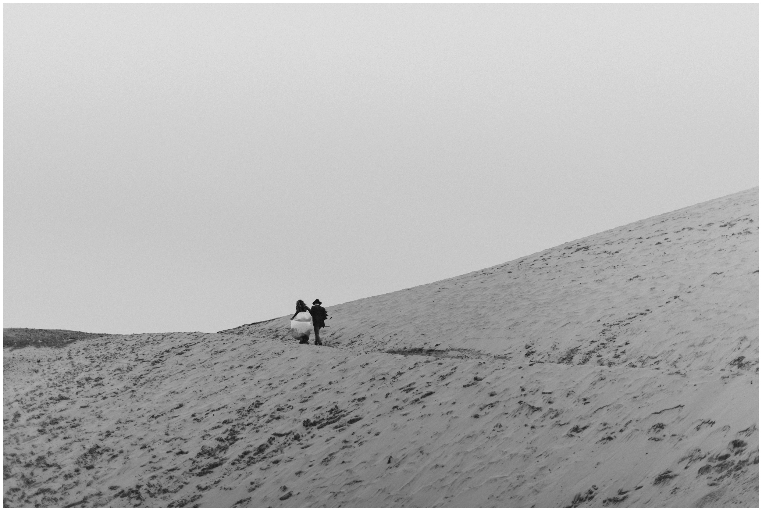 black and white portrait of couple walking up sand dunes  | Pacific City Wedding Photographer www.riversandroadsphotography.com