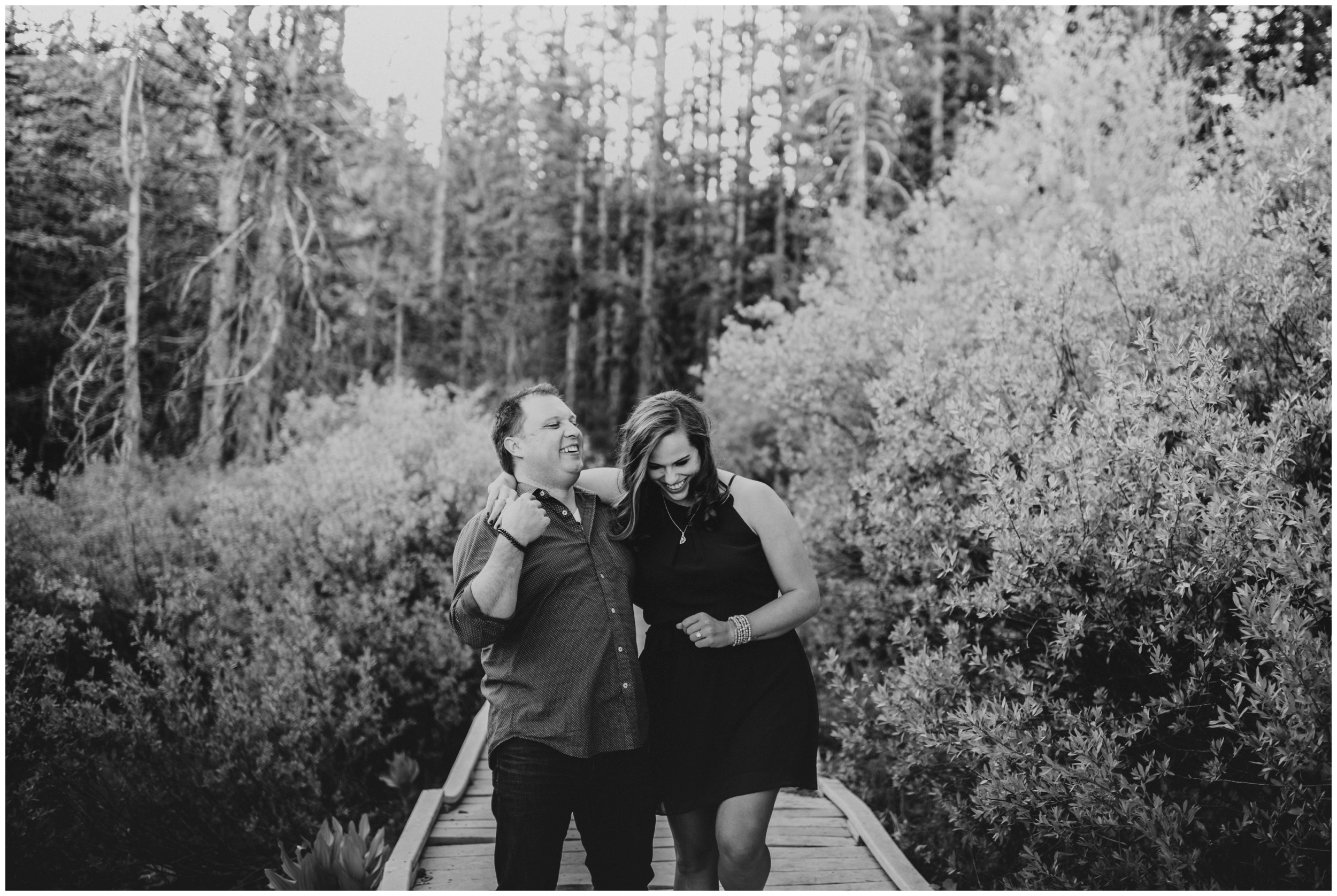 couple laughing and walking on a bridge at Tony grove campground. engagement photographer Logan utah.