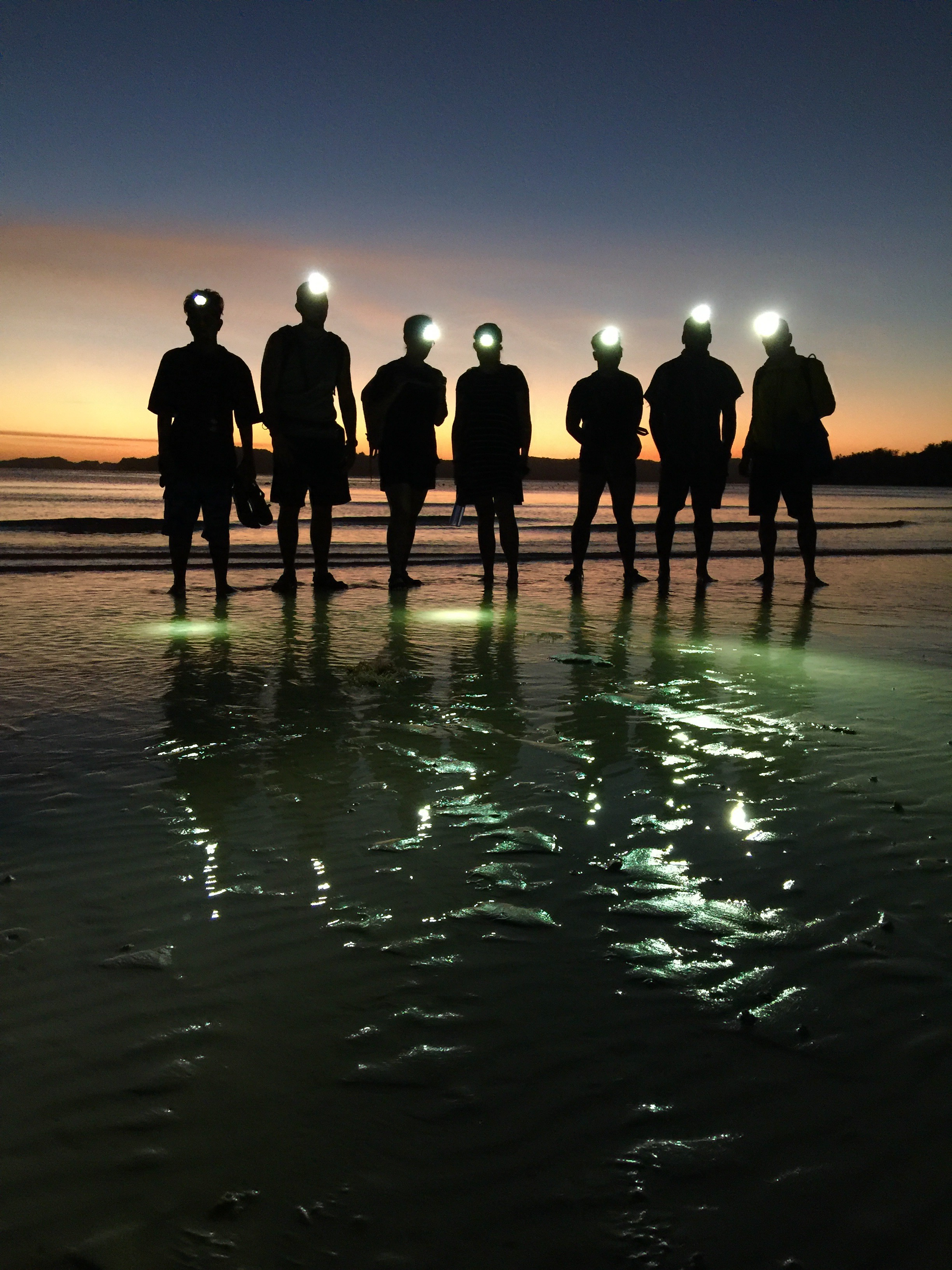 The team poses with their headlamps in front of the backdrop of a typical awe-inspiring sunset off the coast of Ilin Island.