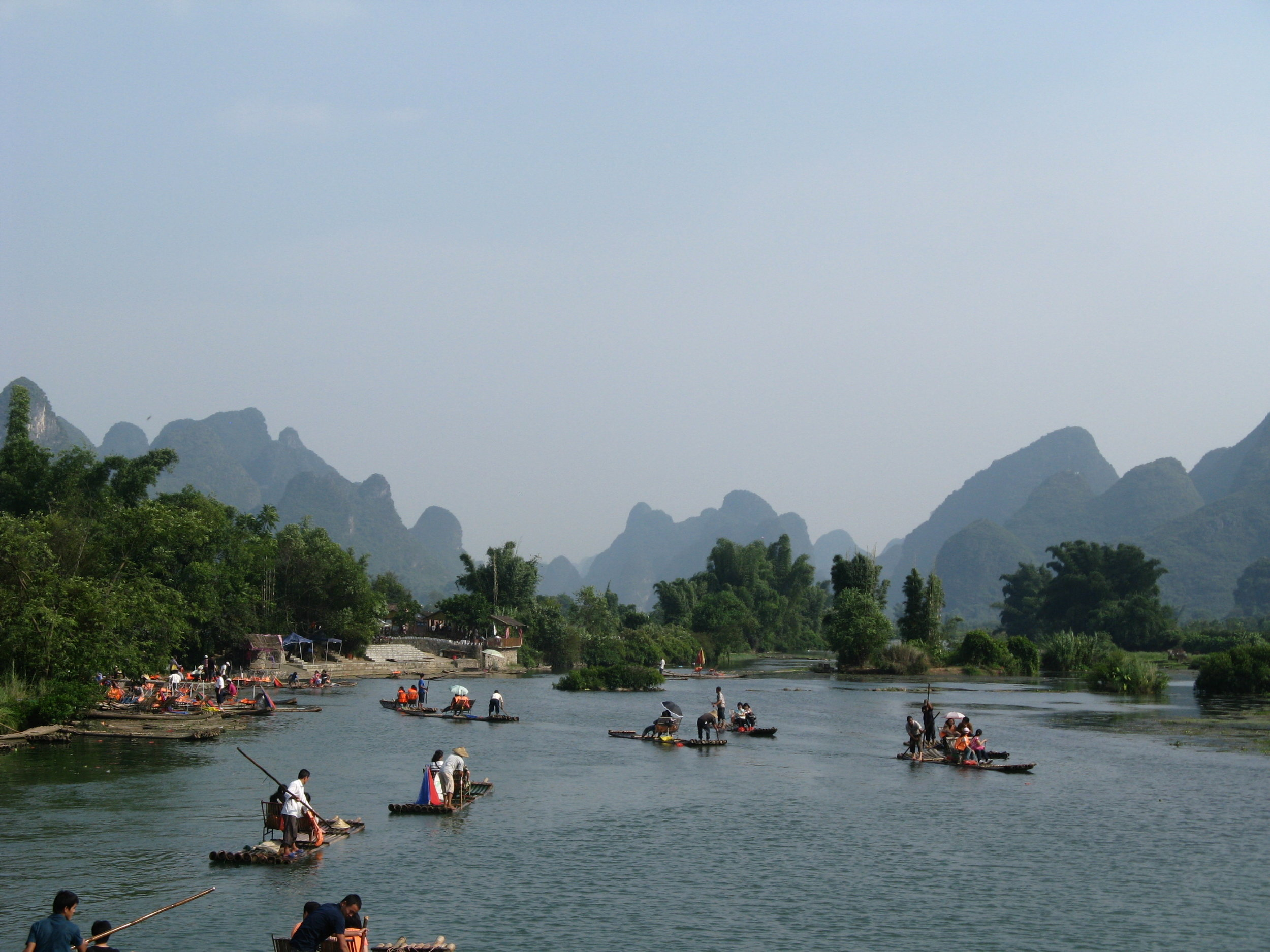 Take a leisurely Bamboo Raft down the Dragon River flanked by some imppressive karst mountains