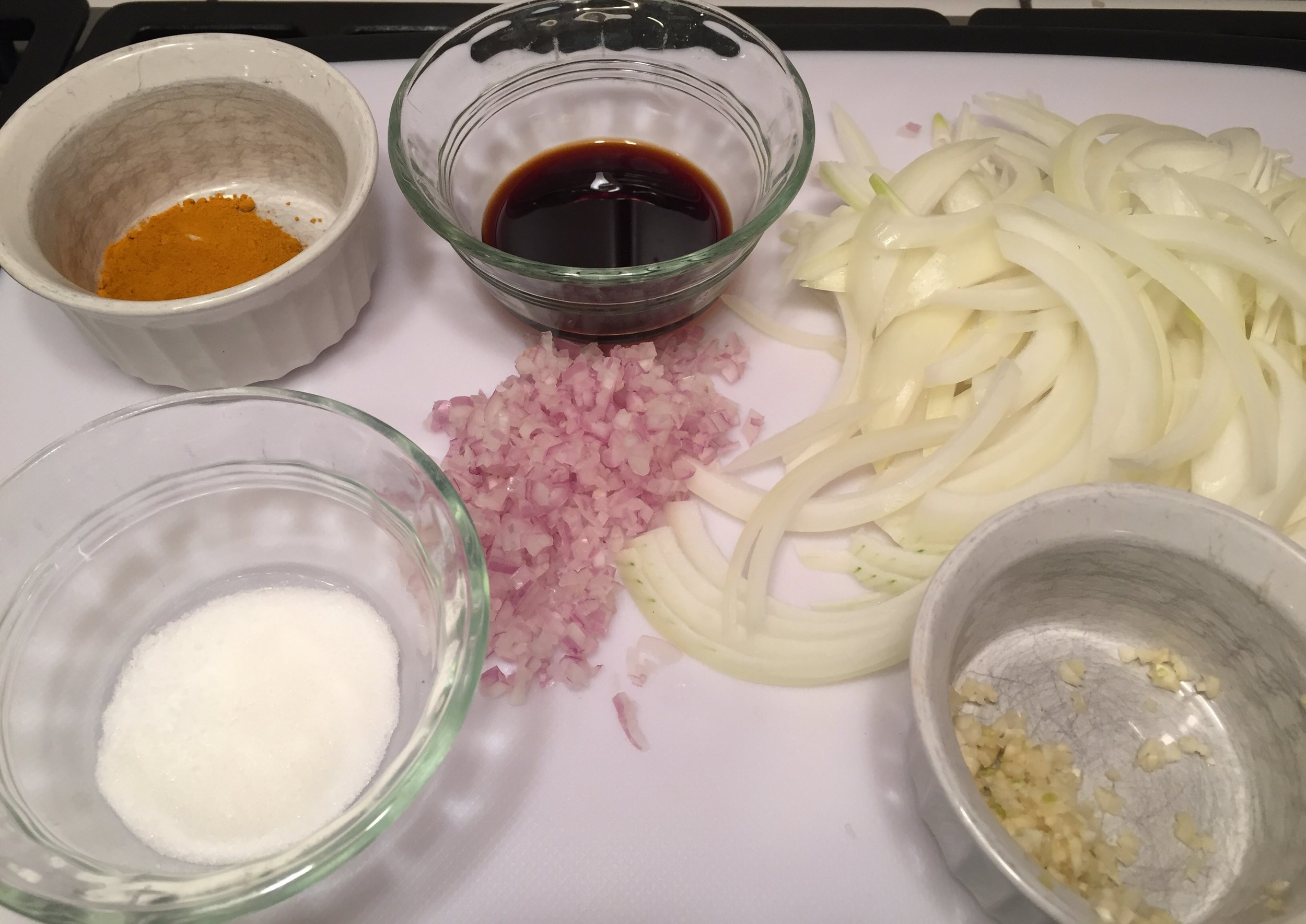 tumeic, soy sauce and sugar for the marinade., Onions shallots and garlic for a saucepan.
