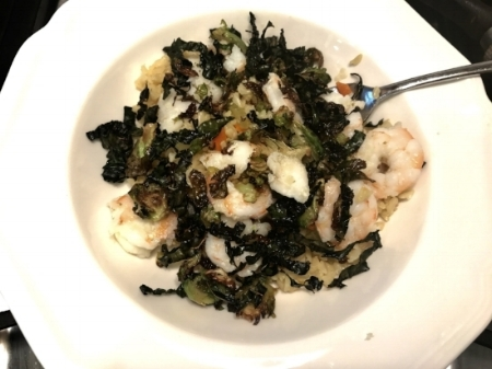 Brown rice bowl with shrimp, fish, garlic, roasted cauliflower and red onion with kale and shaved brussels sprouts as a topping.