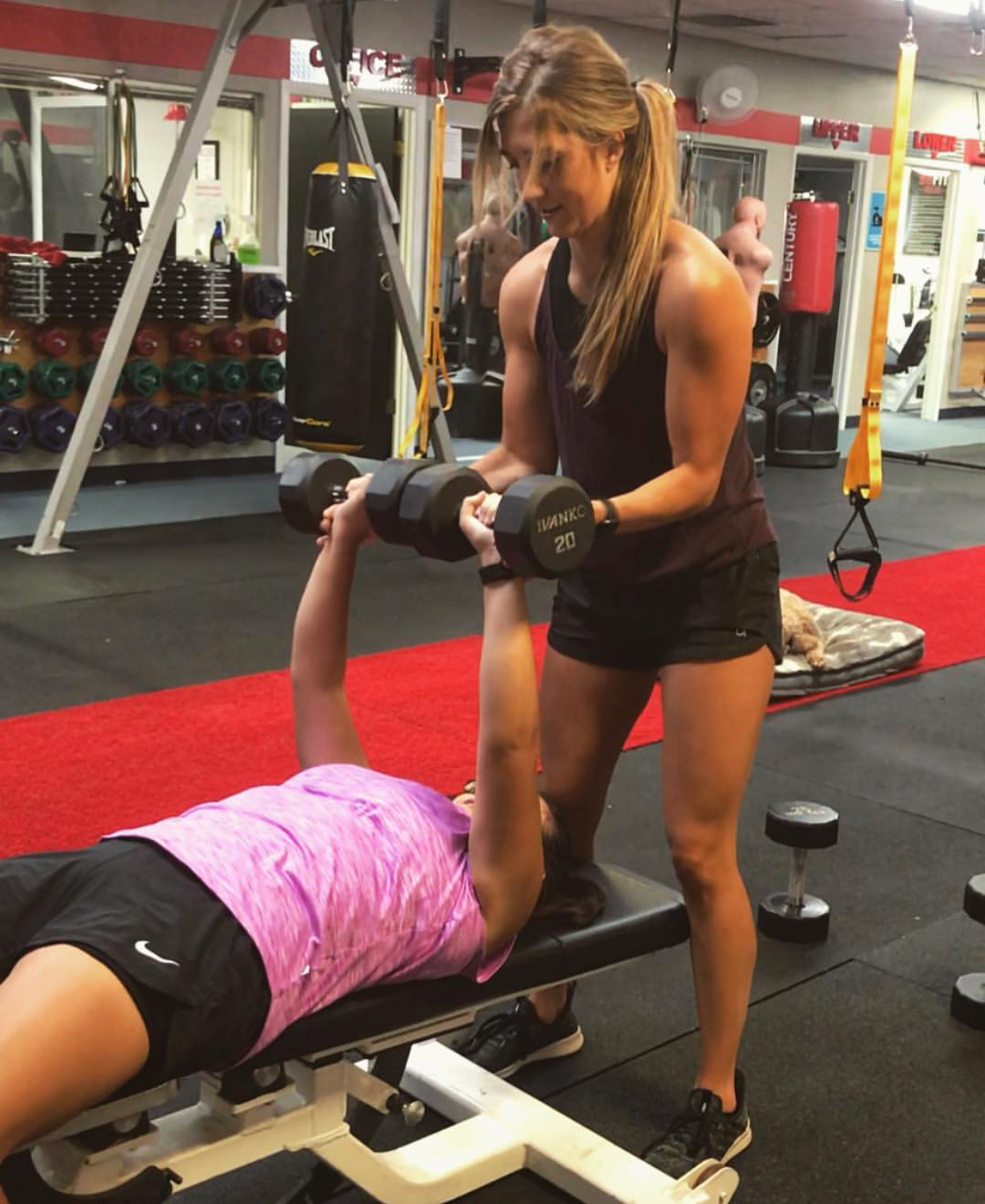 Kayla Schumann, NASM Certified Personal Trainer spotting a client (Above)