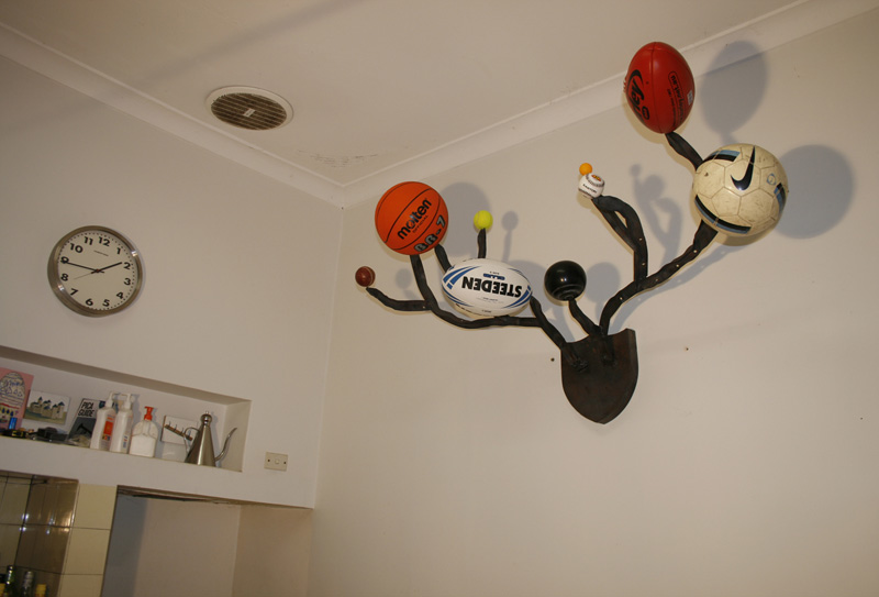 Bruce Slatter,  Gaining Territory (Kitchen version),  2011, Steel, Star Pickets, Sporting balls, 85 x 145 x 70 cm