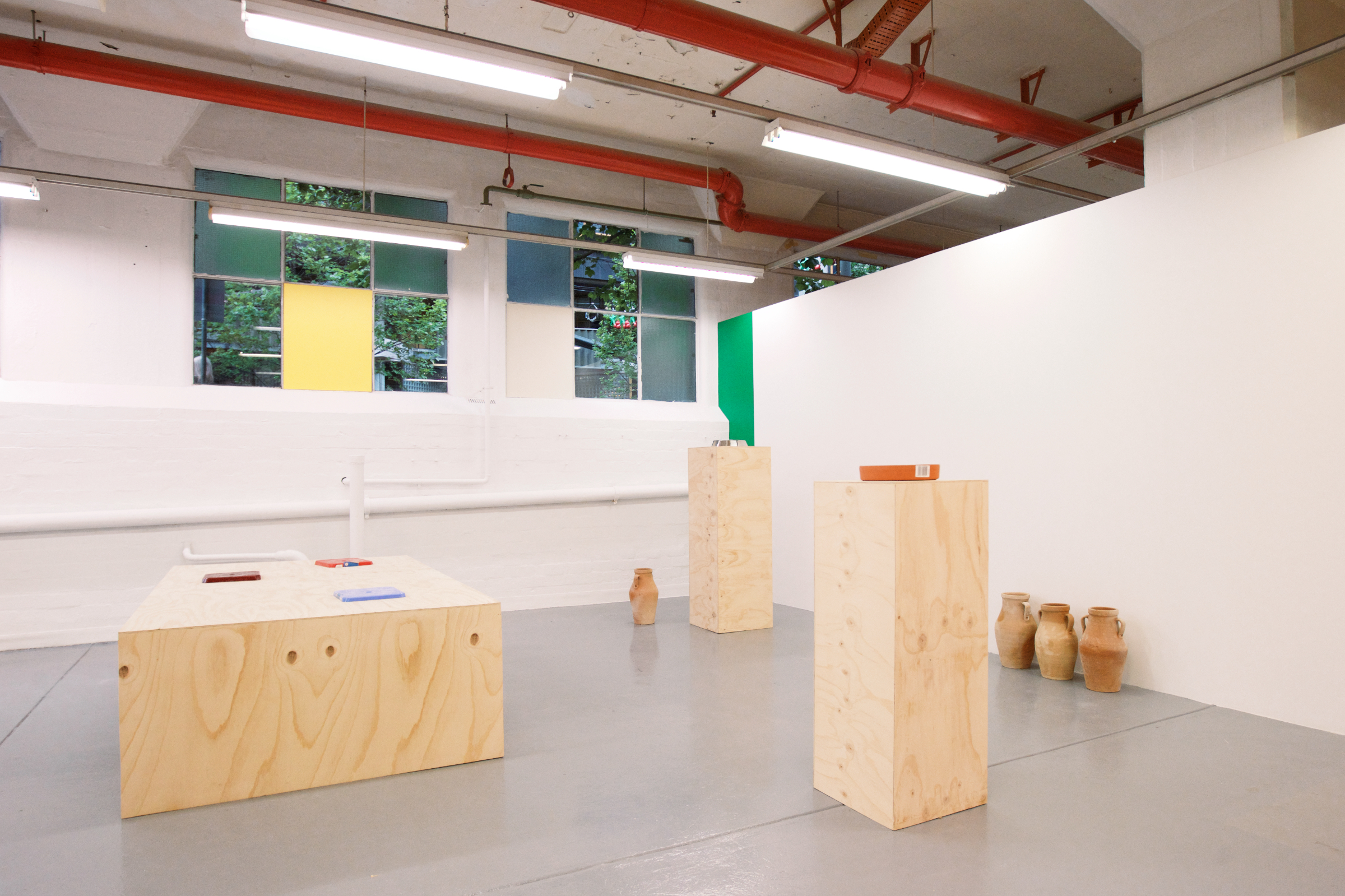 Penelope Moye, Partial install shot of  Receivers  exhibition,L-R: Stools, 2016,  plywood, plastic stools, 58 x 118 x 201 cm, Aut nihil, 2016,  acrylic paint on eight MDF boards, dimensions variable, Untitled, 2016,  four  terracotta jugs, dimensions variable, Vacancy, 2016, acrylic paint, dimensions variable, Dog's bowl, 2016,  plywood, stainless steel, 125 x 41 x 41 cm, Pot, 2016,  plywood, terracotta pot, 107 x 38 x 38 cm. Photo credit: Andy Hattan