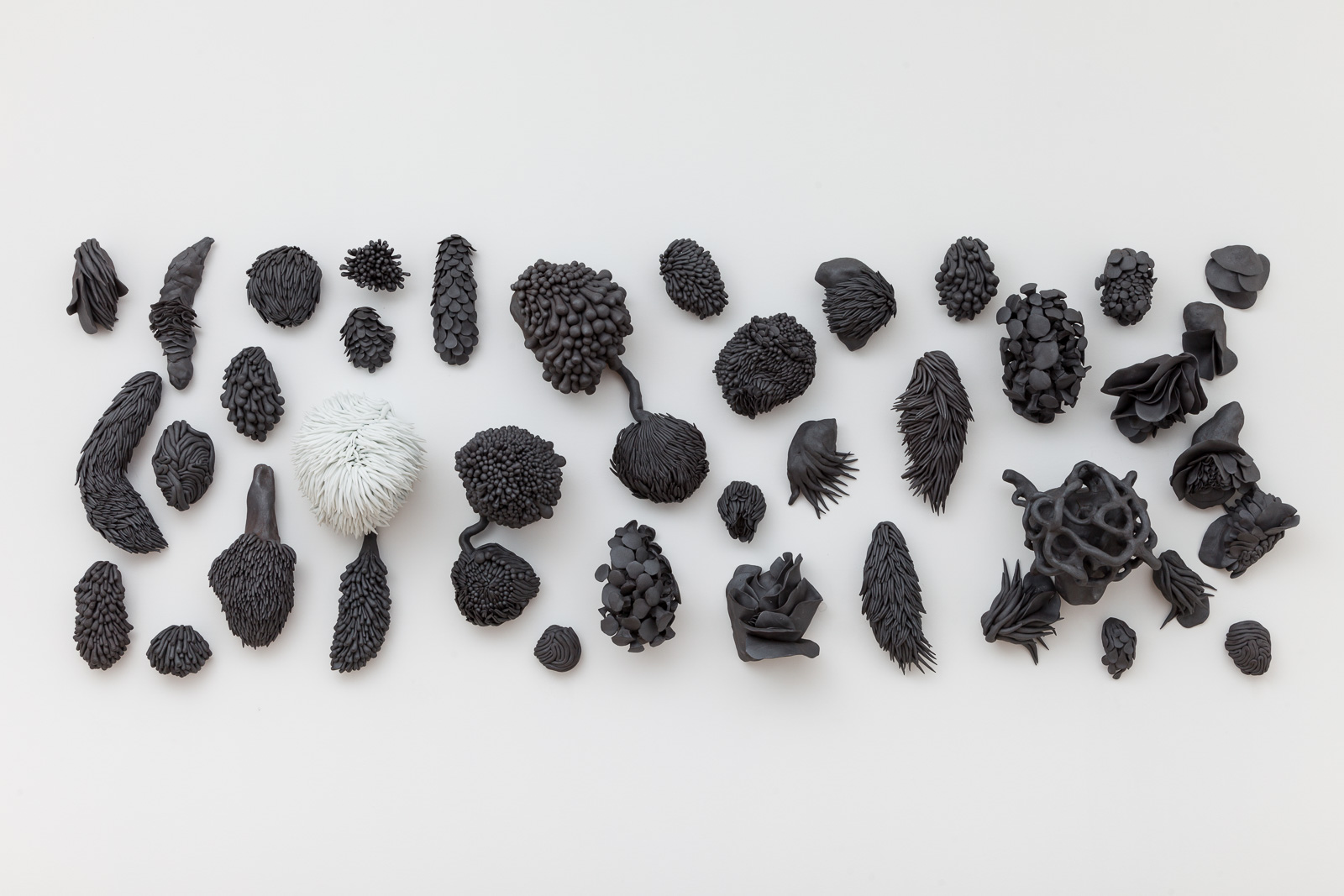 Juz Kitson,  Black sands, ethereal dreams. They are the reeds that bend in the storm,  2018. Porcelain with oxide. 58cm (H) x 1.63m (L) x 18cm (W).