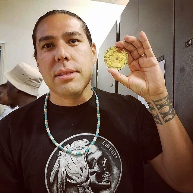 @dallasgoldtooth holding a coin (nelson mandela's nobel peace price) while wearing a coin i painted.. juss dope #levels