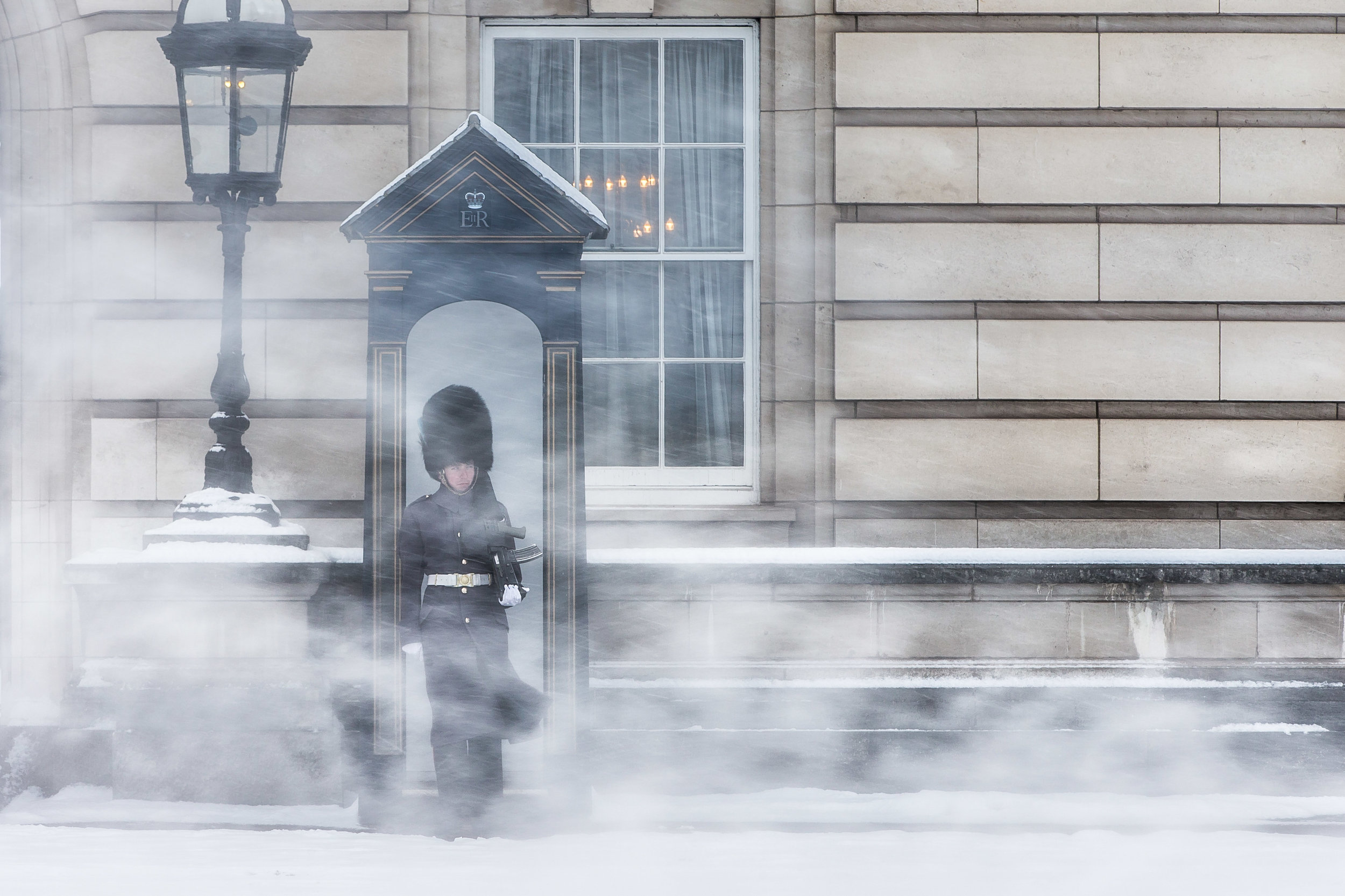 A Foot Guard from the Irish Guards Regiment outside Buckingham Palace during Storm Emma which covered the UK in snow in the winter of 2018. London, England - February 28 2018.