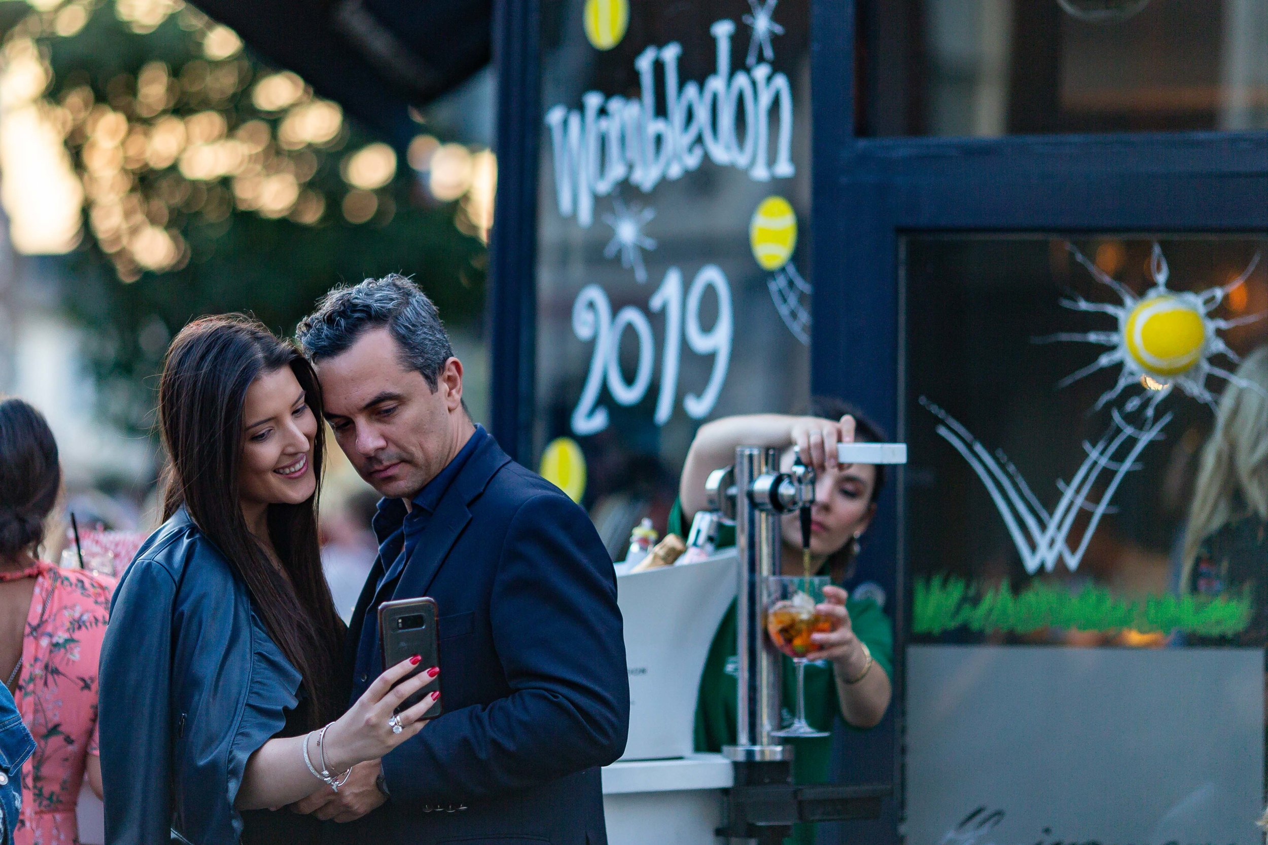 A couple interacts, as a bar lady pours a glass of Pimm's, after watching Roger Federer beat Rafael Nadal in four sets to reach Wimbledon men's final, on the 12 July in Wimbledon Village, London.