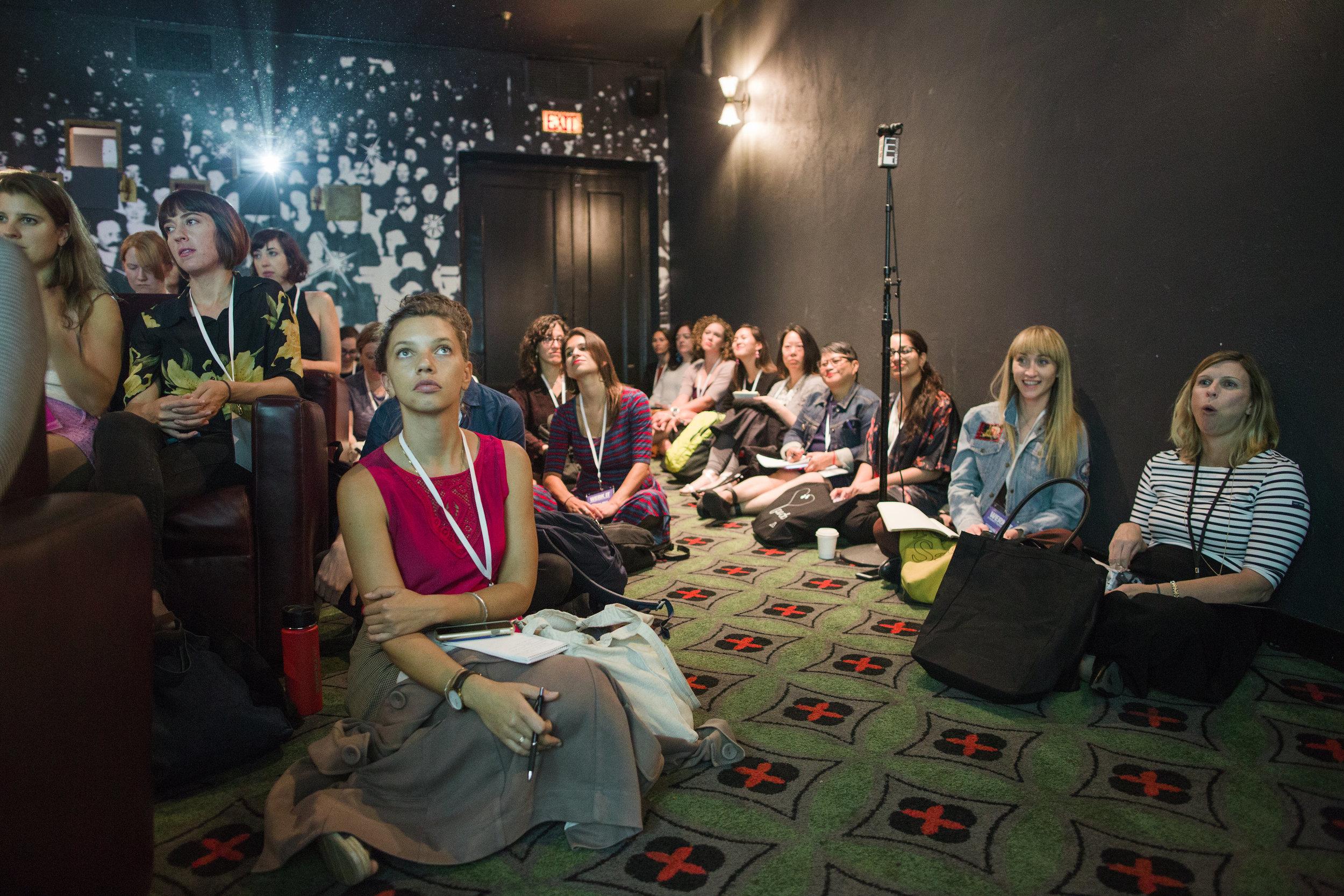 Audience members watching a presentation