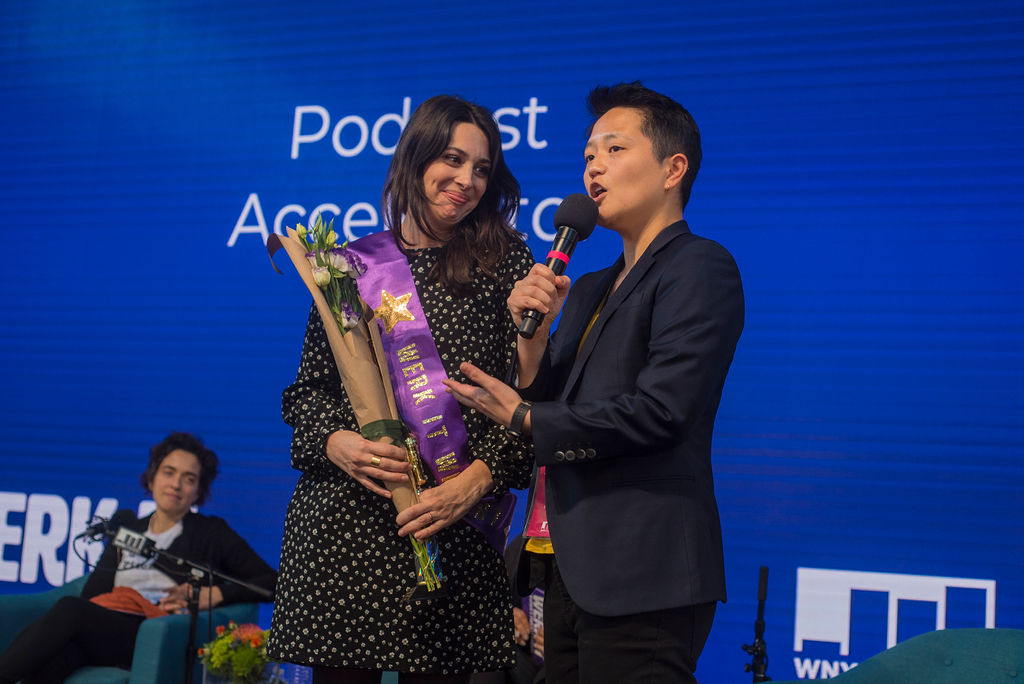 Kathy Tu presenting an award on stage to the Podcast Accelerator winner