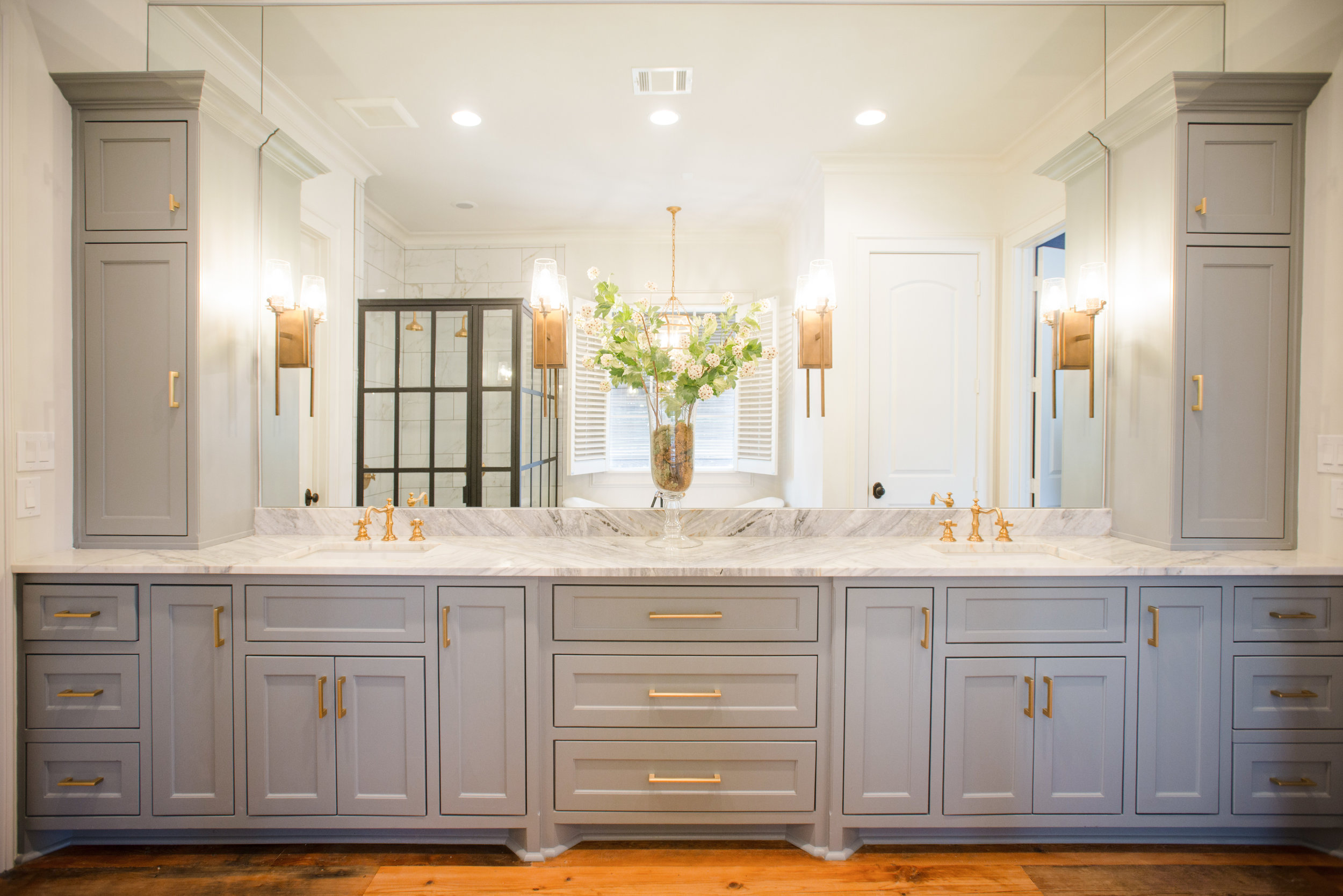 We used a beautiful grey on the cabinets that really compliments the gorgeous super calcatta slab on top.  Brushed gold faucets, sconces and hardware.