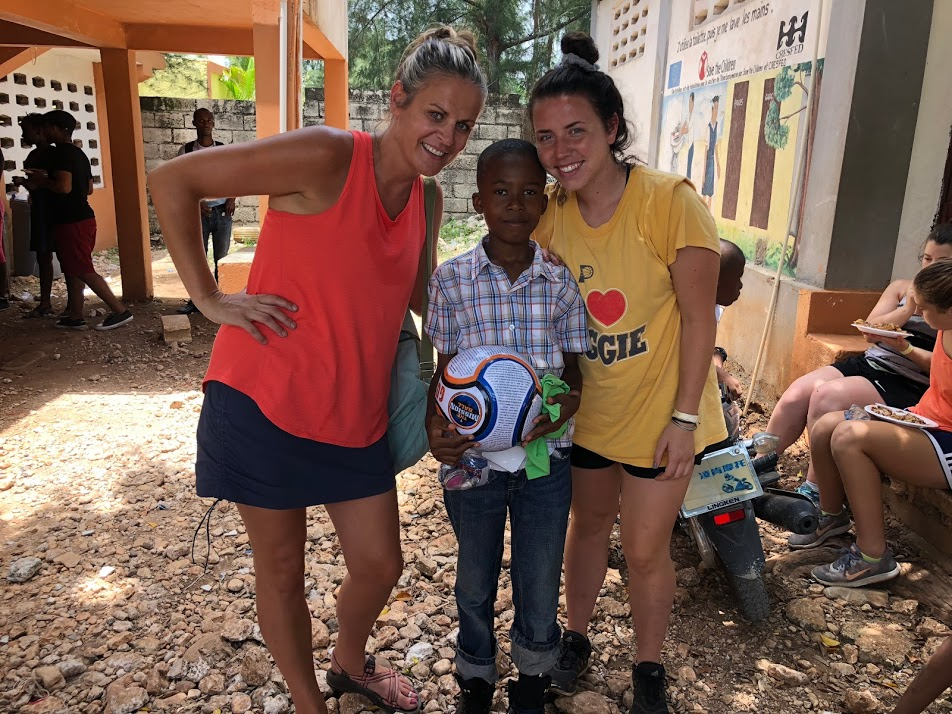 Meghan and Savannah present a Gospel ball to their new Haitian Friend.