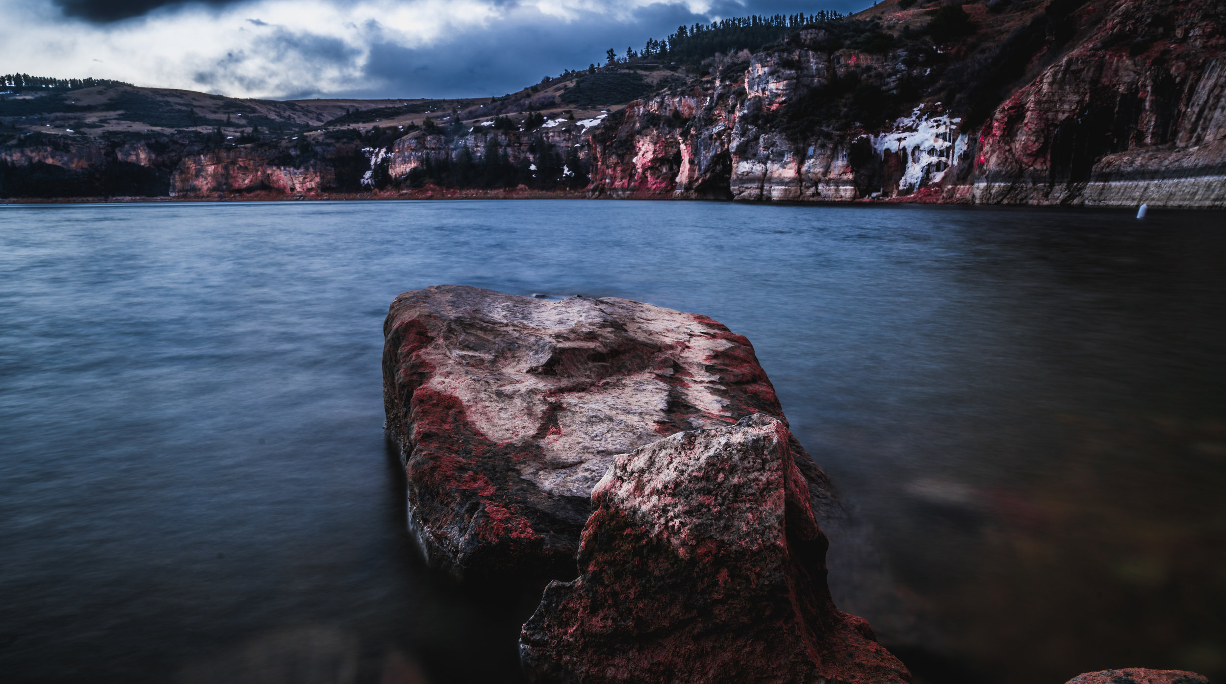 An isolated rock protrudes from the frigid waters of the Bighorn Canyon