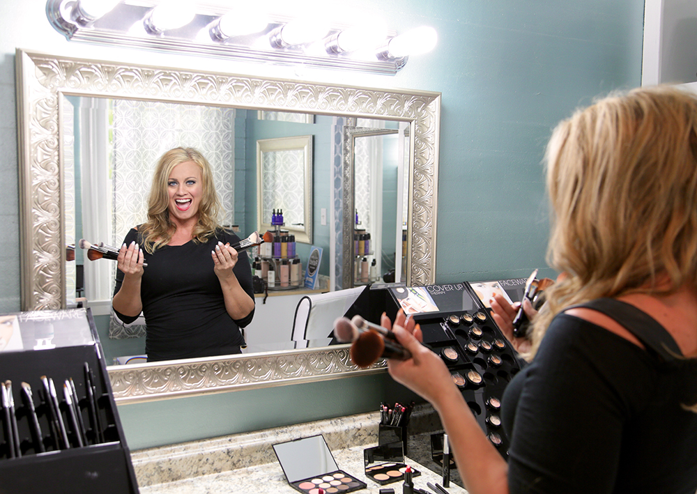 Image of Lorri Bolander founder of Key West Hair and Makeup surrounded by makeup and holding blush brushes.