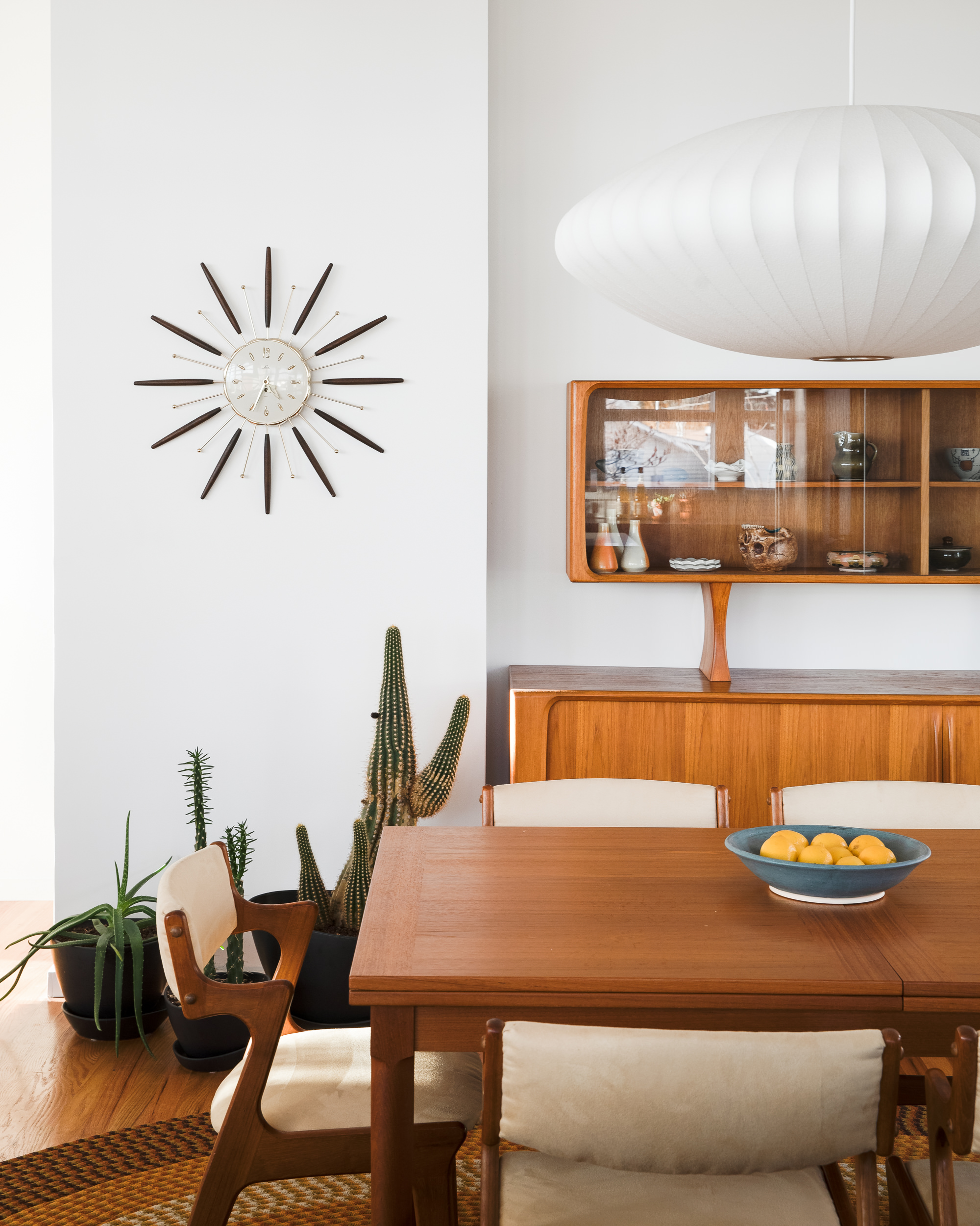 In the dining area, a  George Nelson Bubble Lamp  hangs above a vintage  Skovmand & Andersen dining table and vintage  Dyrlund  dining chairs. A  Lux Starburst clock  hangs on the wall next to a vintage  Bernhard Pedersen and Son  sideboard and hutch. The hutch is home to ceramics by Mudpuppy Ceramics ,  Jamie Kelly , Angus Graham, and  John Cohorst .