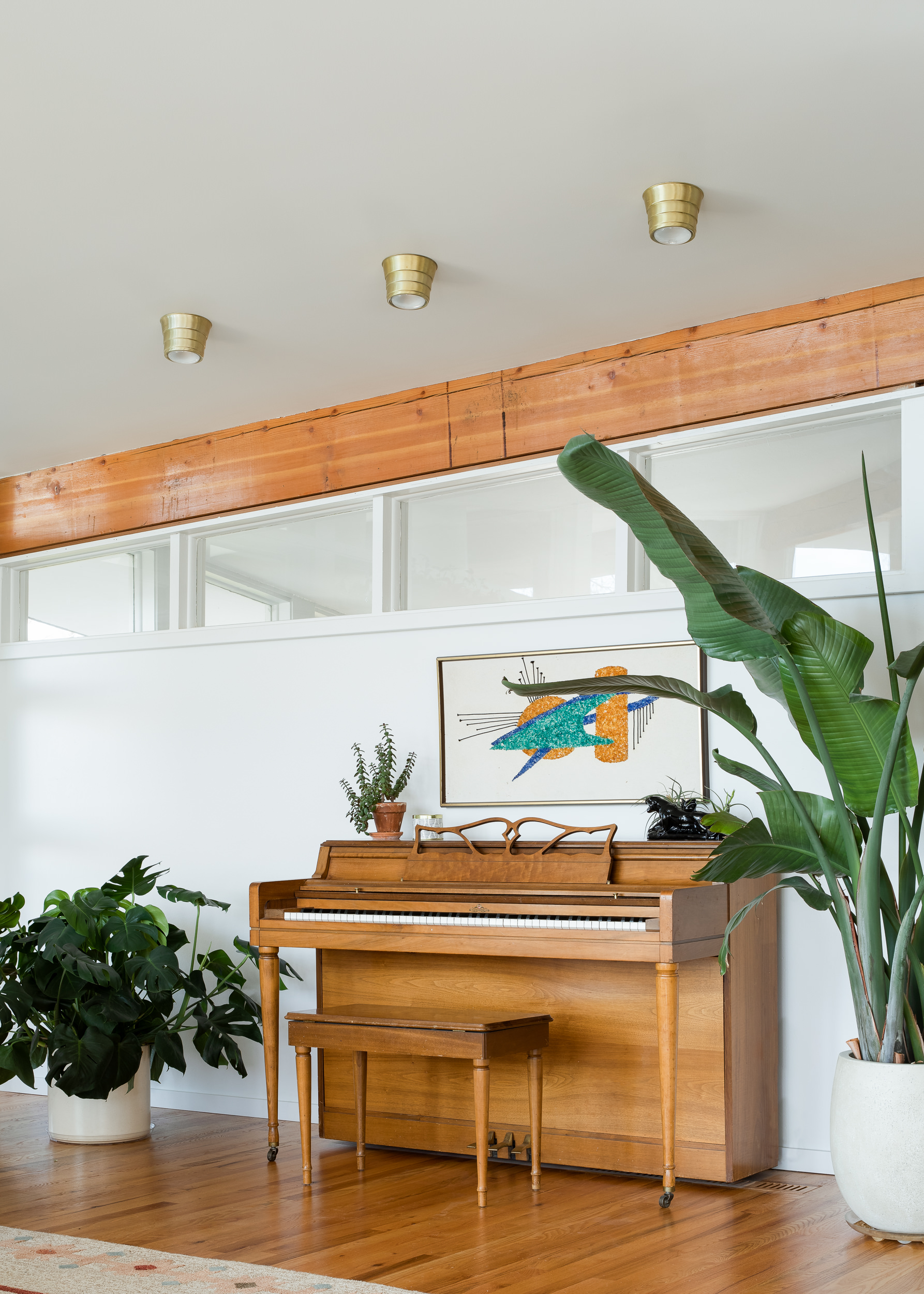 A piece of atomic gravel art hangs above a  Wurlitzer Spinnet piano  in the living room.