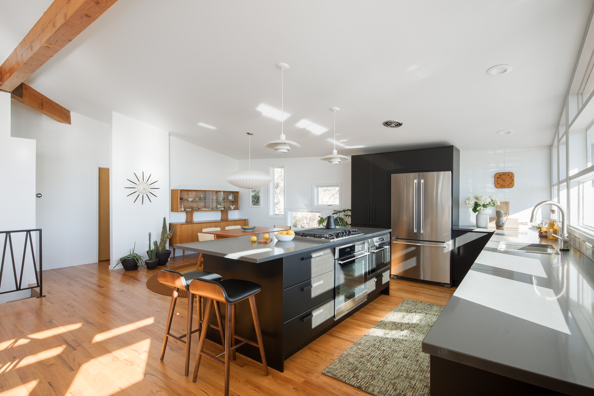 The couple removed a wall to create the open kitchen and dining area.  Ikea  cabinets form an L-shape around the perimeter.  Article Sede barstools  line the island and  Poul Henningson PH4/3 Lights  hang above.