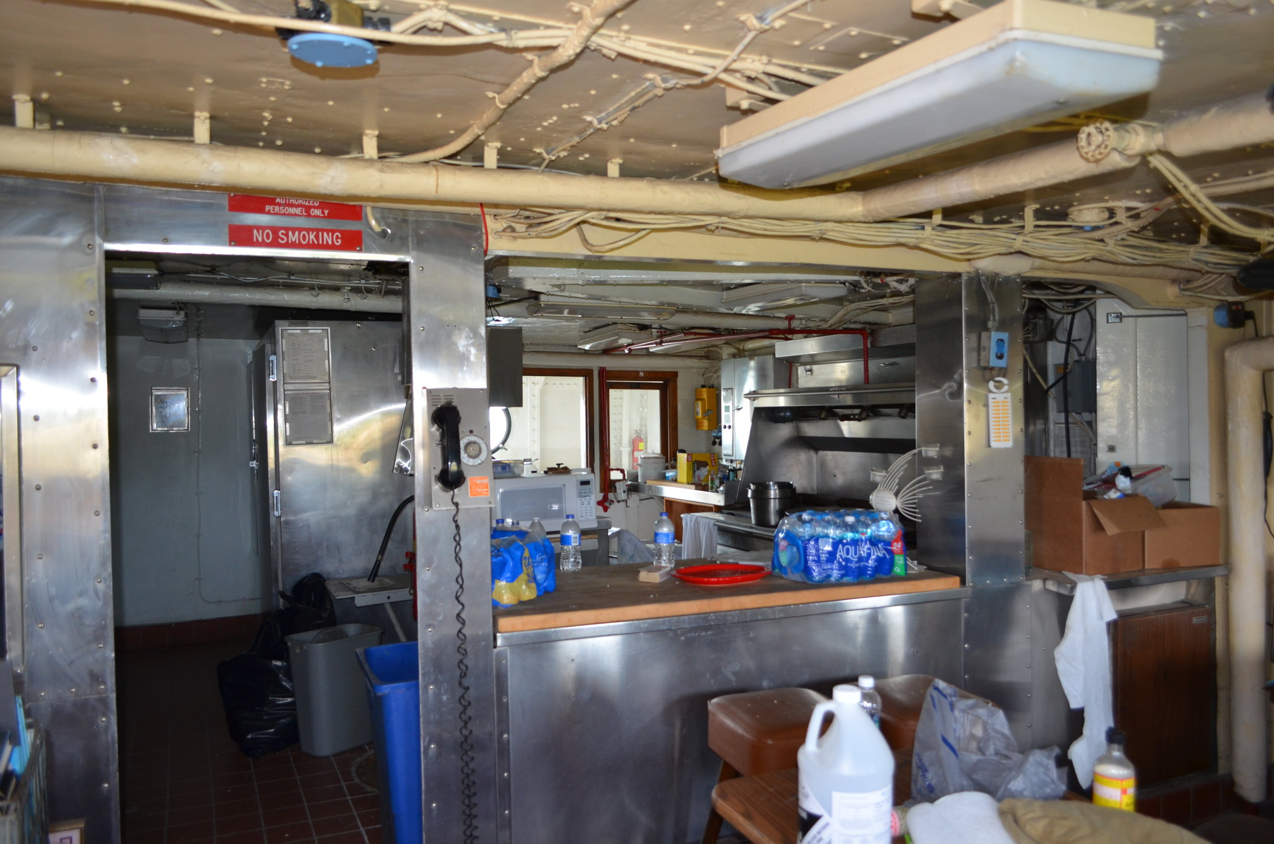The refrigerator/freezer bank is to the far left. The stove/sinks are to the far right. A steam table in the center is where crew served themselves.