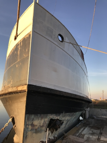 The first coat of primer is applied to the hull above the splash zone.
