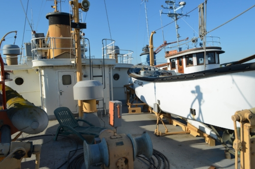 """Former Boat Deck as seen from the aft rail. A 1940s """"crew boat"""" is the tender to starboard. Parts of more modern inflatable is seen to port."""