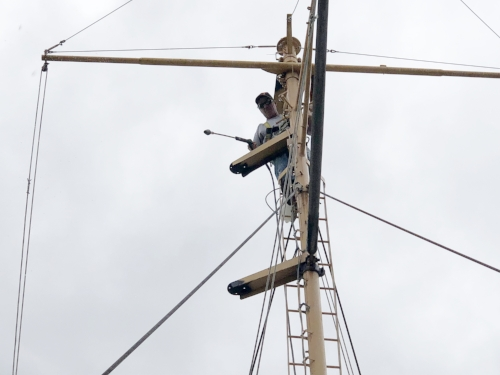 Chris pressure washes the aft mast in preparation for priming.