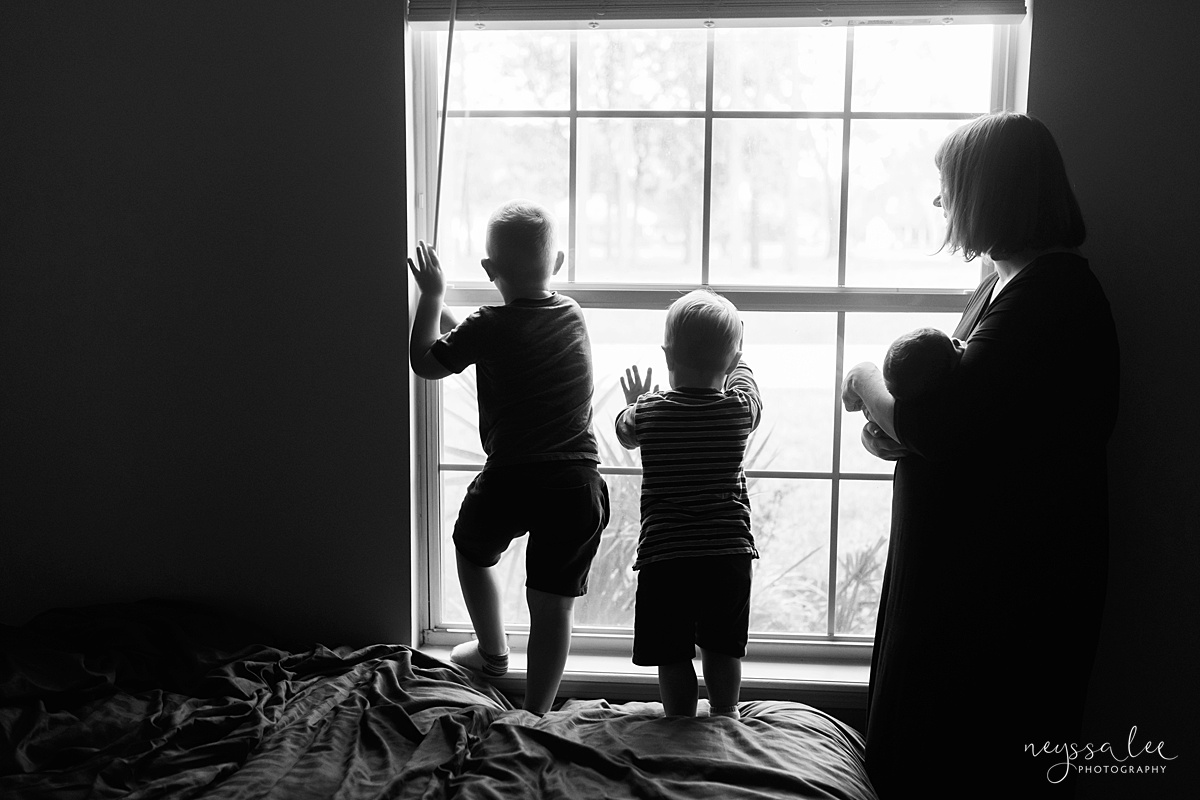 Seattle newborn photographer, Neyssa Lee Photography, Lifestyle Newborn Photography, black and white photo of kids looking out window with mom and baby nearby