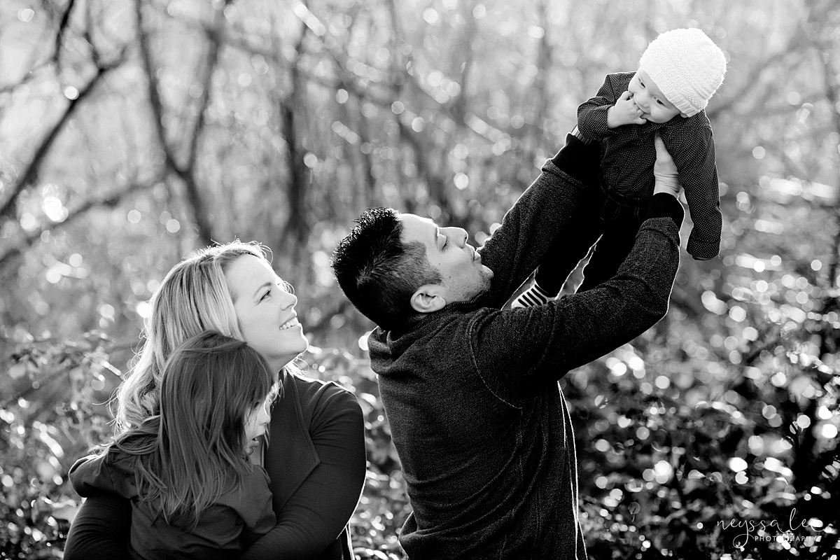 Uncooperative Kids During Family Photos, Neyssa Lee Photography, Seattle Family Photographer, Issaquah Photography, Black and white photo of family of four with dad lifting baby into the air