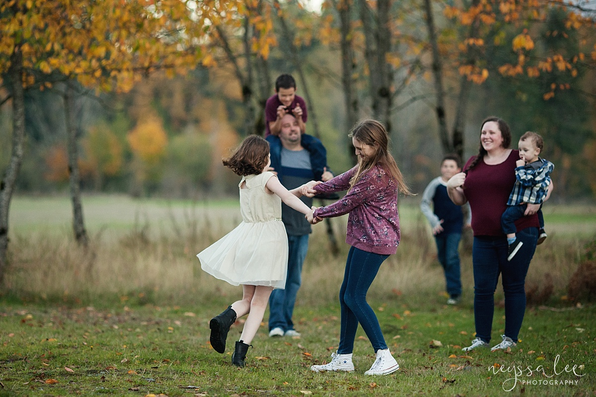 What to Wear for family photos, Family Outfit Color inspiration, Neyssa Lee Photography, Seattle Family Photographer, Photo of girls dancing together with family in the background, blue and maroon color inspiration