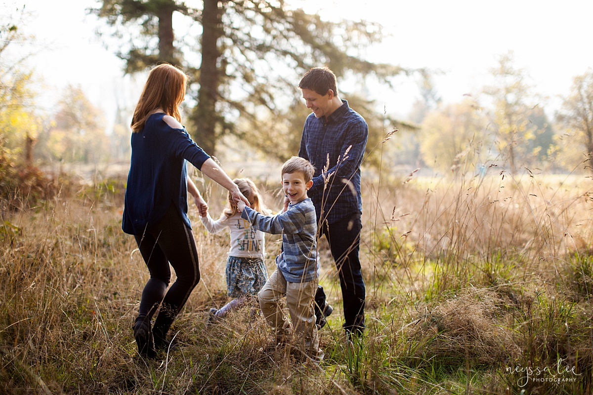 What to Wear for family photos, Family Outfit Color inspiration, Neyssa Lee Photography, Seattle Family Photographer, Photo of a family of four in a field playing ring around the rosie