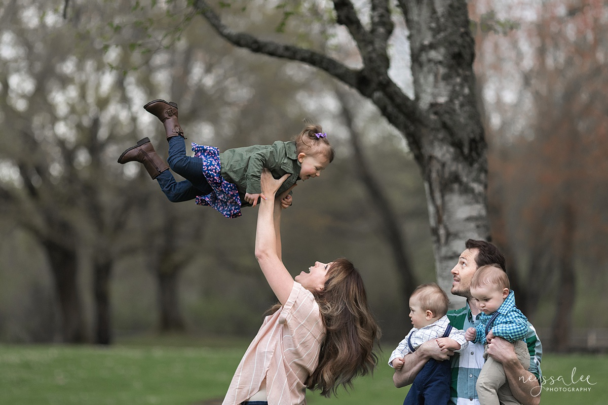 Neyssa Lee Photography, Issaquah Family Photographer, Family Photos with Grey Skies, Photo of mom tossing daughter in air as dad with twins watches nearby