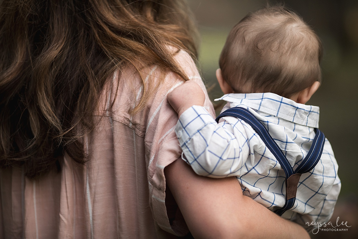 Neyssa Lee Photography, Issaquah Family Photographer, Family Photos with Grey Skies, Lake Sammamish State Park, Photo of baby boy lovingly holding onto moms hair