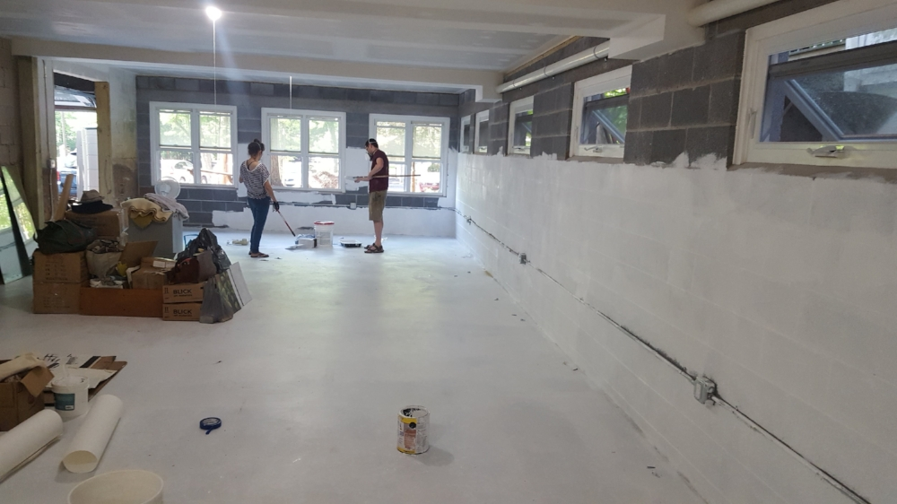 This space is pretty much brand new. This image shows a continuation of the space shown above. Volunteers above paint the space white in preparation for its first use in 2016. An overhead door allows for easy move of large scale items in and out of the studio.