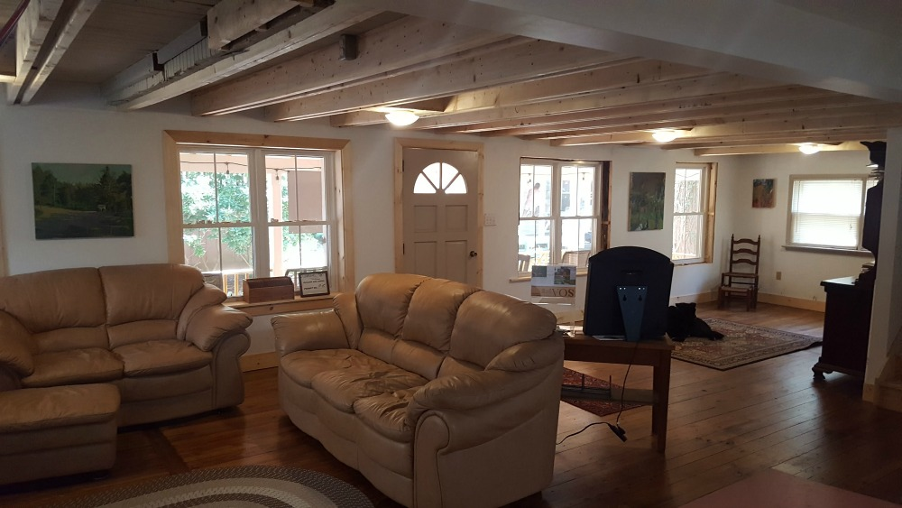 These images are of the large common area of the cottage. Small bedrooms are located upstairs, and there are two bathrooms.
