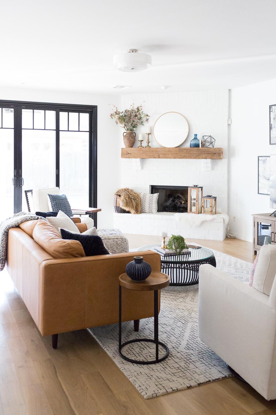 Tulsa-Remodel-Reveal-Modern-White-Farmhouse-black-windows-and-doors-modern-leather-sofa-article-sven-sofa-white-brick-fireplace-wood-beam-mantle-t.jpg