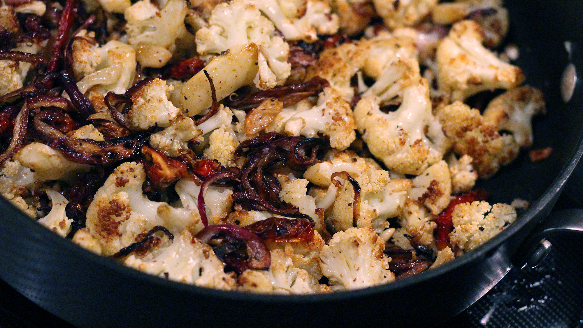 The cauliflower starts in the oven to give it it's crispy, delicious taste, but it's finished in a sauté of the caramelized onions, sun-dried tomatoes, lemon juice and, eventually, arugula.