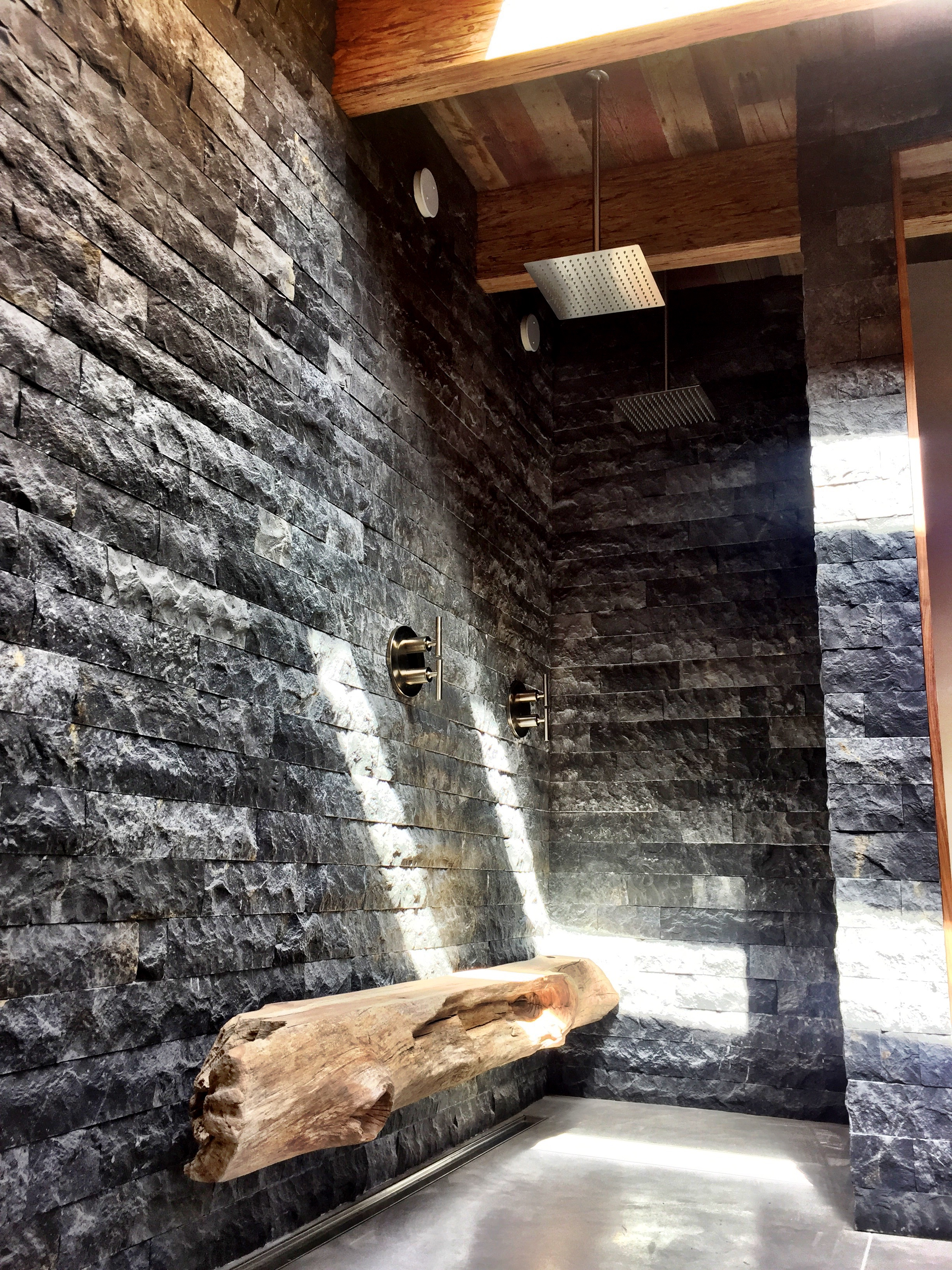 Carmel Highlands master glass-free double rain shower. Big Sur driftwood log, Indonesian stone.