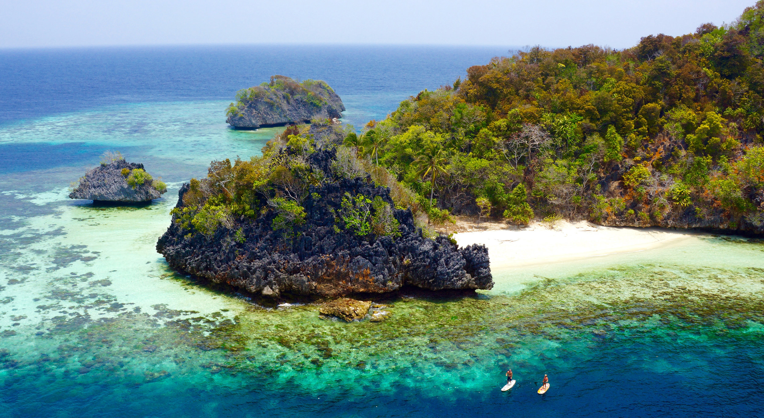Stand up paddleboarding around a little island in Raja Ampat Indonesia, only accessible by private boat.