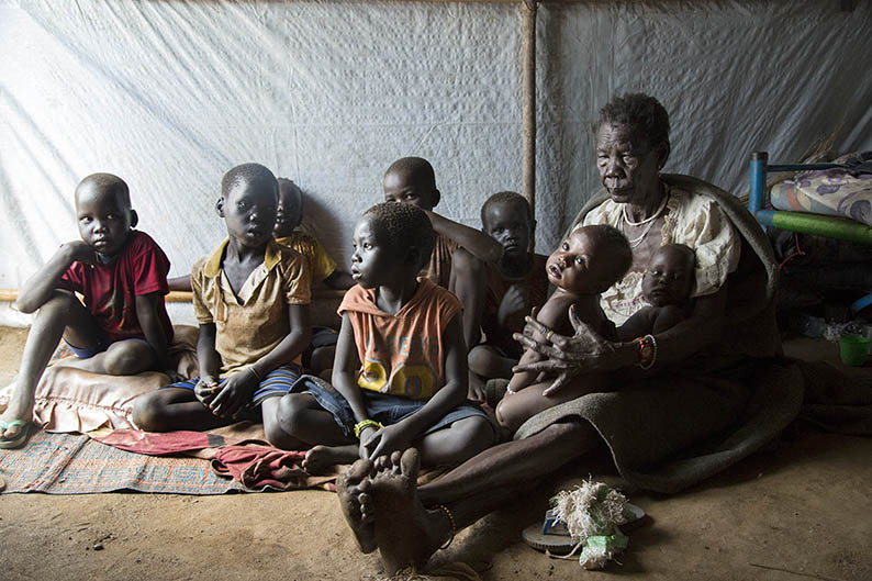 A grandmother sits with her nine grandchildren at a refugee camp in South Sudan, Ilana Rose for World Vision