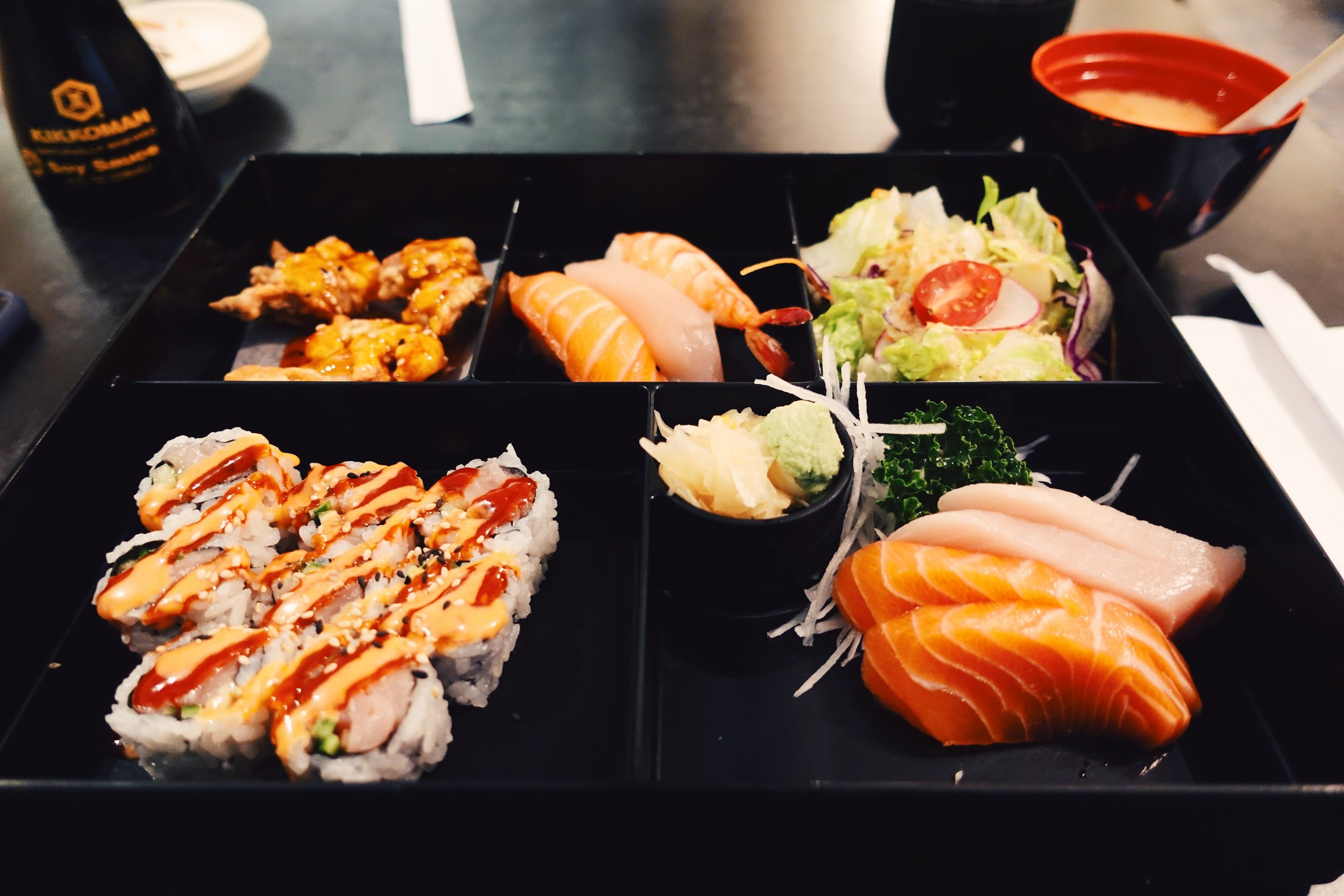 Sushi and Sashimi Bento - From top left - Daily feature, sweet Thai chicken nuggets, nigiri, salad, spicy tuna roll, and sashimi. Comes with miso soup.