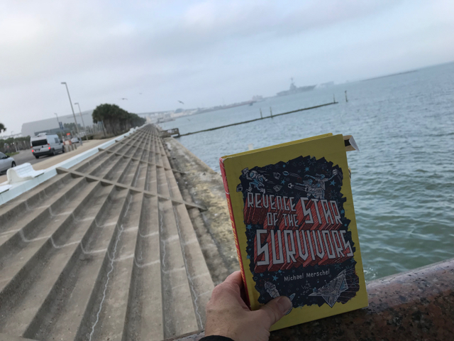 """We might have been singing """"Under the Boardwalk"""" as we tried to take this picture of the book with the aircraft carrier in the background."""