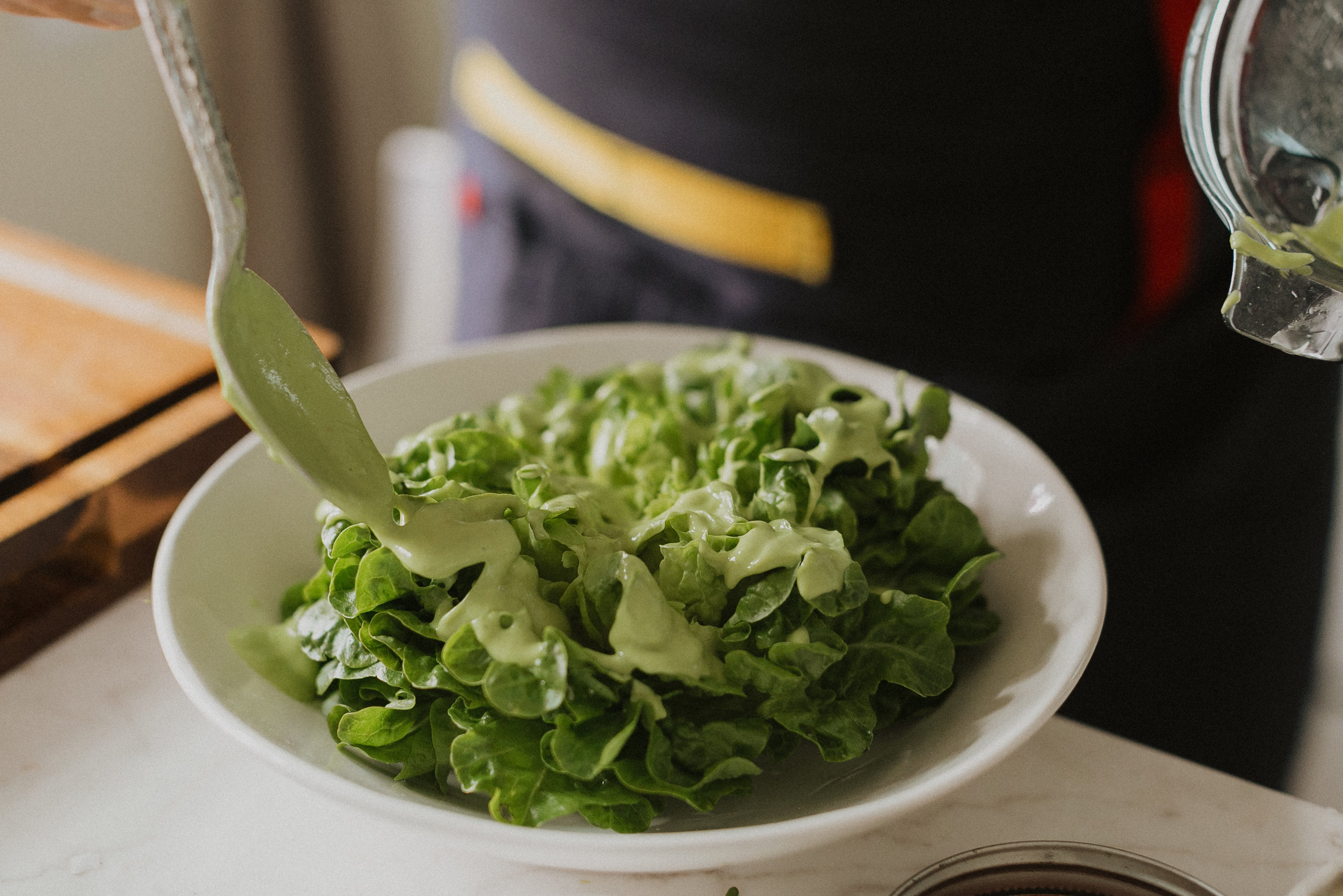 Seamus drizzles Green Goddess Dressing on top of little gem lettuce.