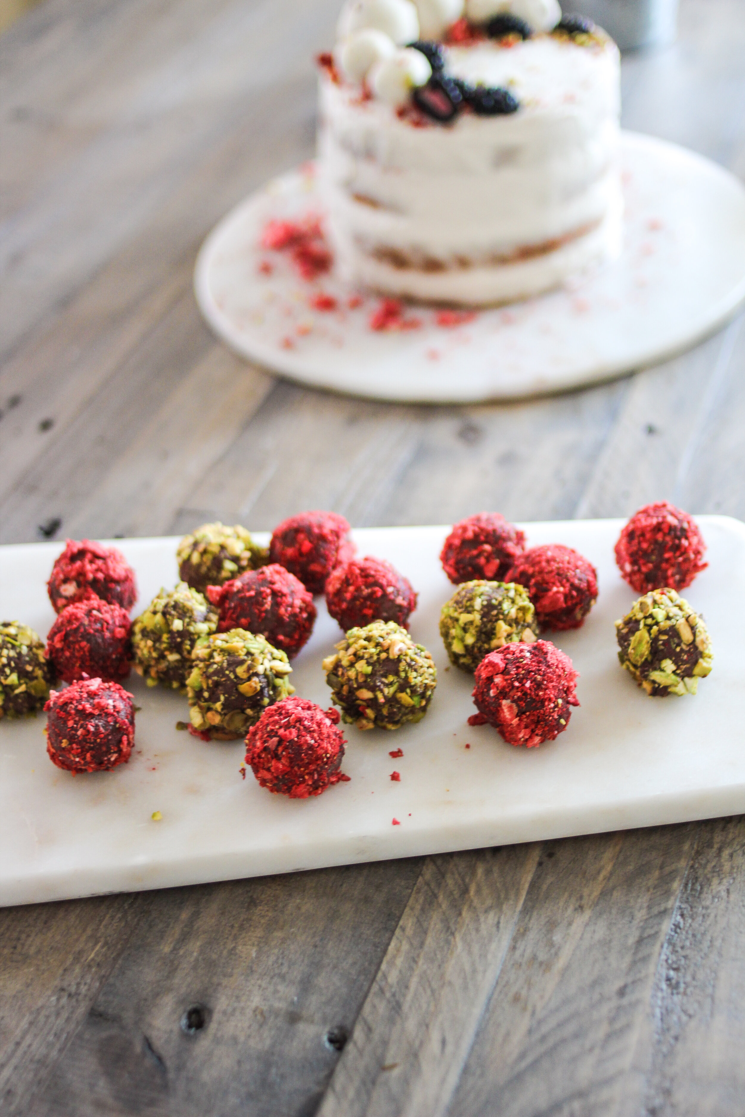 Raw Chocolate Truffles for my birthday this summer, and  Shanti Kitchen  Raw Carrot Cake with Coconut Meat Frosting in the background.