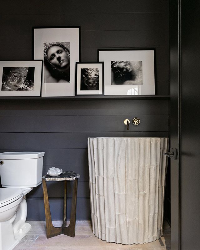 M O O D Y • Sometimes the bathroom is the best space to make an impact on your guests, so why not make it moody and provocative? The custom concrete sink contrasts the dark shiplap to create a luxurious feeling in the powder bathroom.