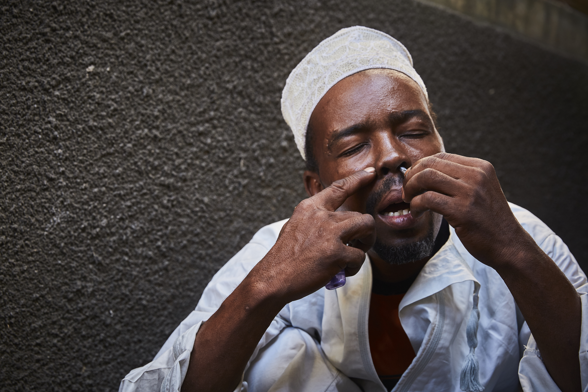 Ali Rajabu, 36years old, prefers to snort the drug. When he started using, he was with good friends. He thought they were going outside to smoke cigarettes but they instead handed him a pipe with  unga  (heroin).  Ali is wearing the traditional Kanzu that men wear before praying at mosque. He wears it to pay respect during Ramadhan, but has not fasted though it is a requirement for Muslims.