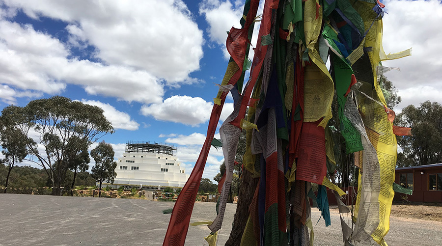 View of the Stupa through wind-whipped prayer flags - photo by Catherine Schieve